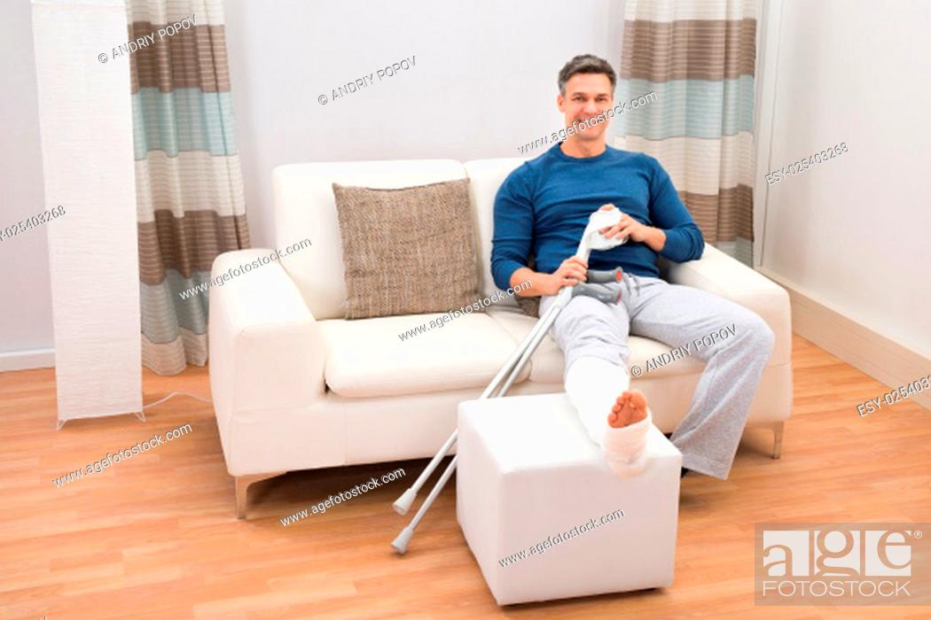 Stock Photo: Portrait Of A Smiling Man Sitting On Sofa With Crutches At Home.
