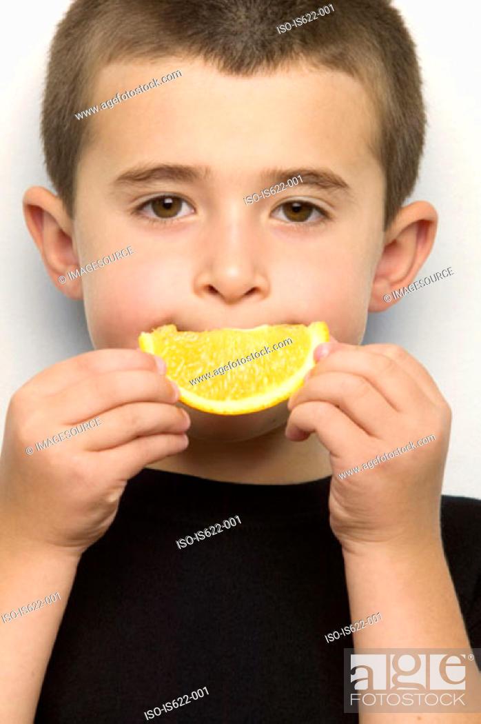 Stock Photo: Boy holding orange segment to mouth.