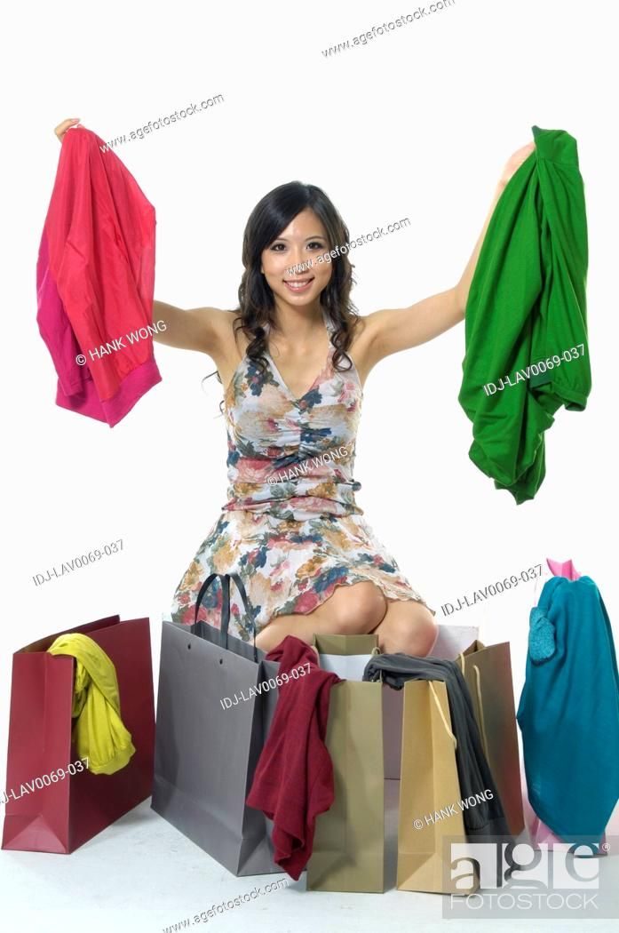 Stock Photo: Woman showing clothes near shopping bags and smiling.