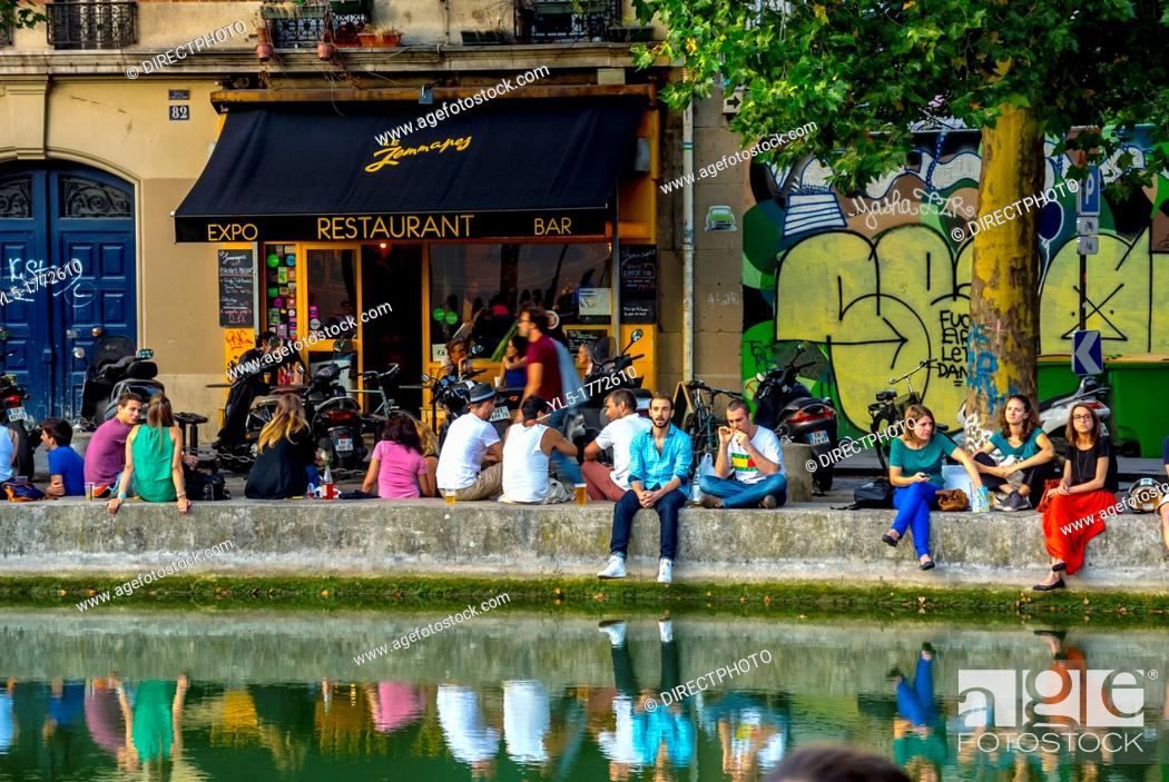 Imagen: Paris, France, Young People Relaxing in Front of French Bar Bistro Restaurant, 'Marcel' the Canal Saint Martin Area.