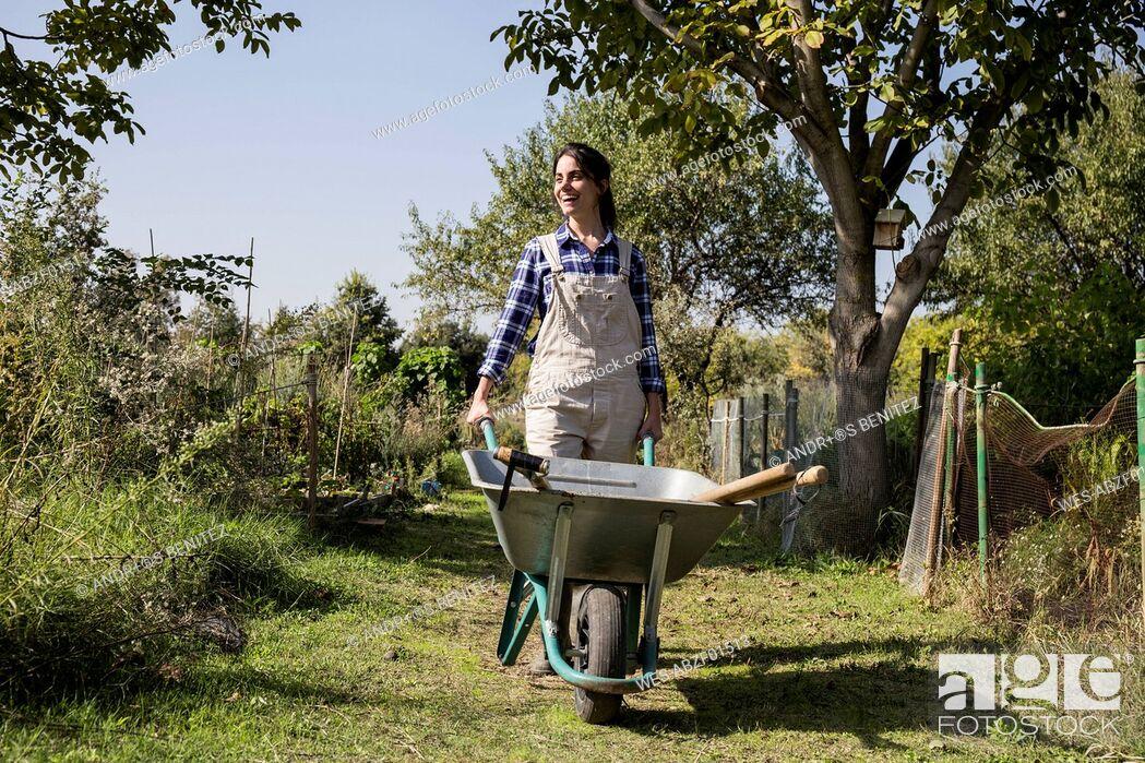 Stock Photo: Woman working on farm pushing wheel barrow.