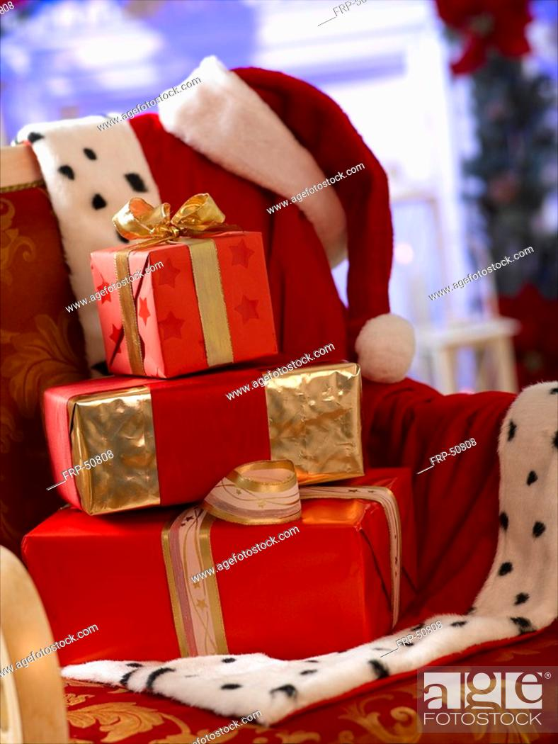 Stock Photo: Christmas gifts and Santa Claus jacket and hat.