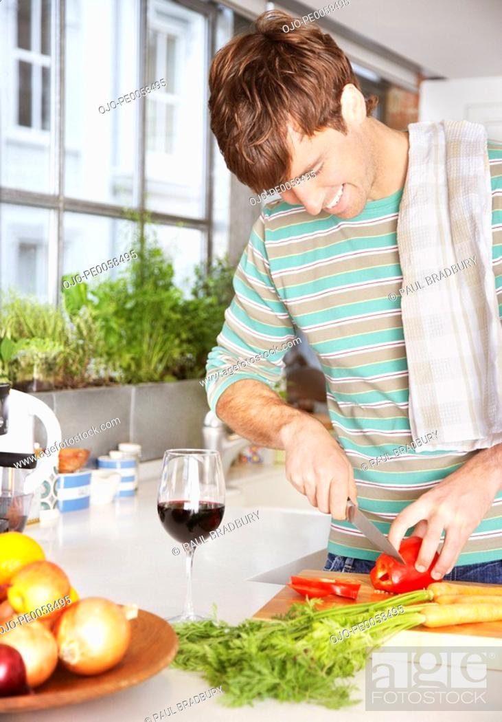 Stock Photo: Man cutting red peppers in a kitchen.