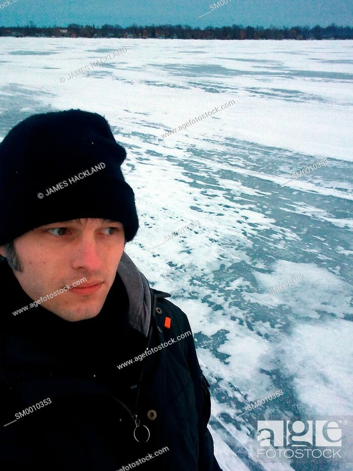 Stock Photo: A man dressed in winter clothing taking a selfie on a frozen lake in the winter. Lake Simcoe, Ontario, Canada.