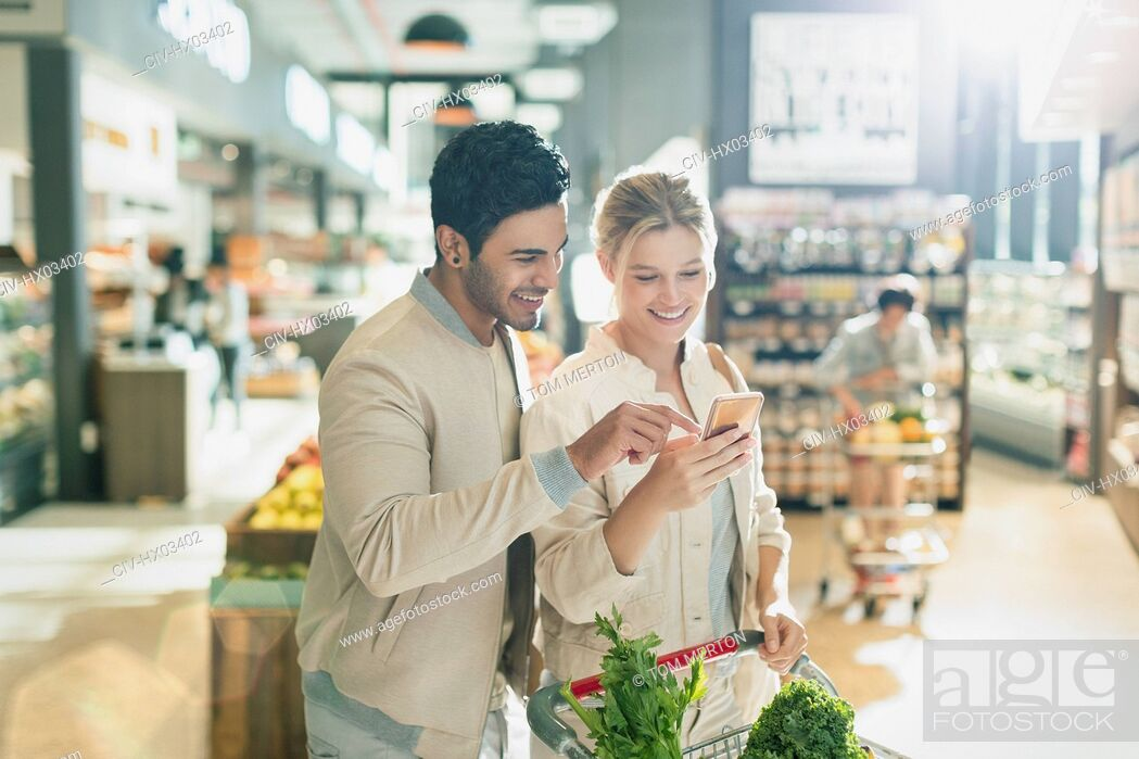 Imagen: Young couple using cell phone, grocery shopping in grocery store market.