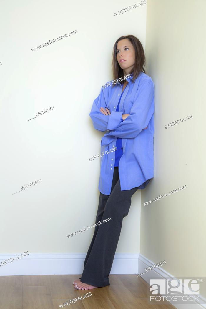 Stock Photo: Young woman leaning against a wall.