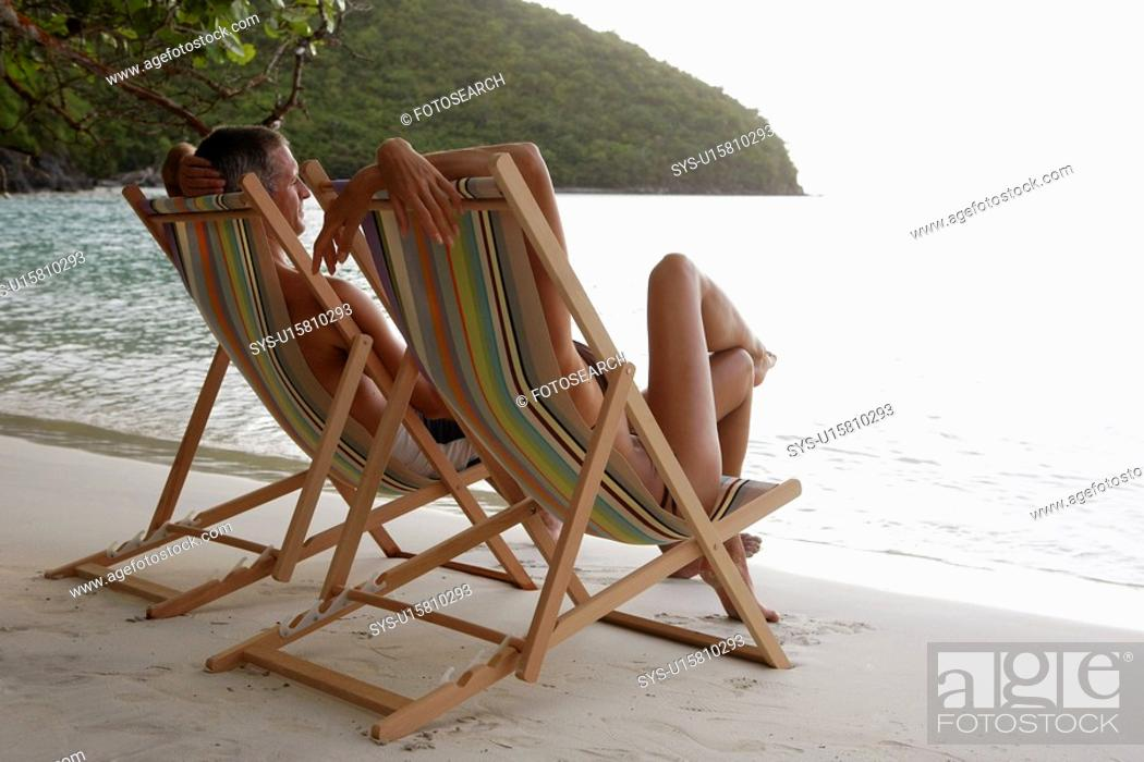 Stock Photo: Mid adult couple on lounge chairs on beach, St. John, US Virgin Islands, USA.
