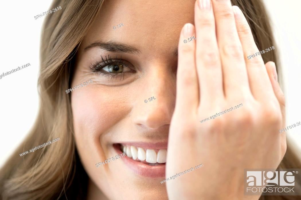 Stock Photo: Mid adult woman covering eye with hand.