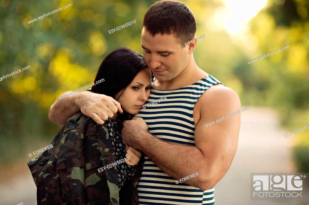 Woman and soldier in a military uniform say goodbye before a