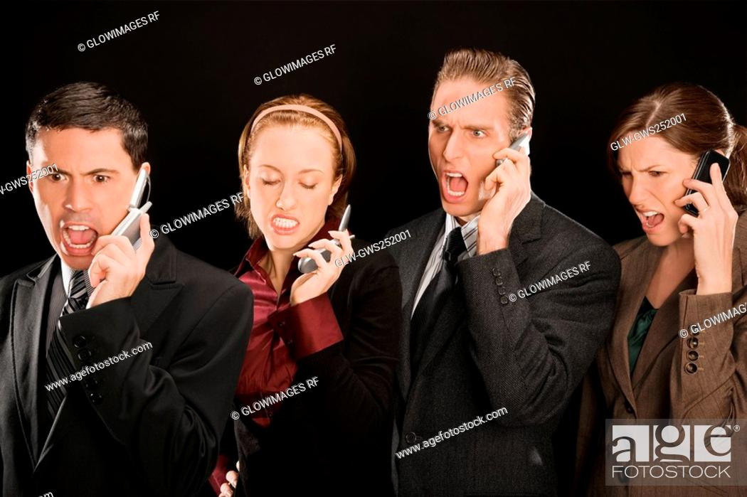 Stock Photo: Four business executives talking on mobile phones.