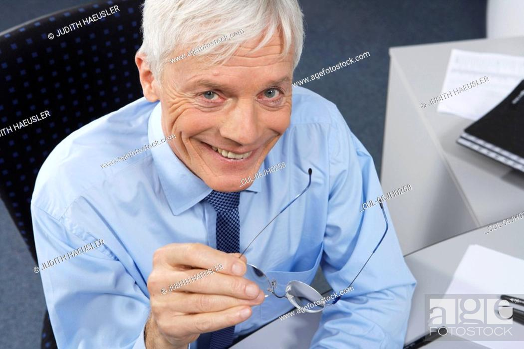 Stock Photo: Mature businessman on desk.