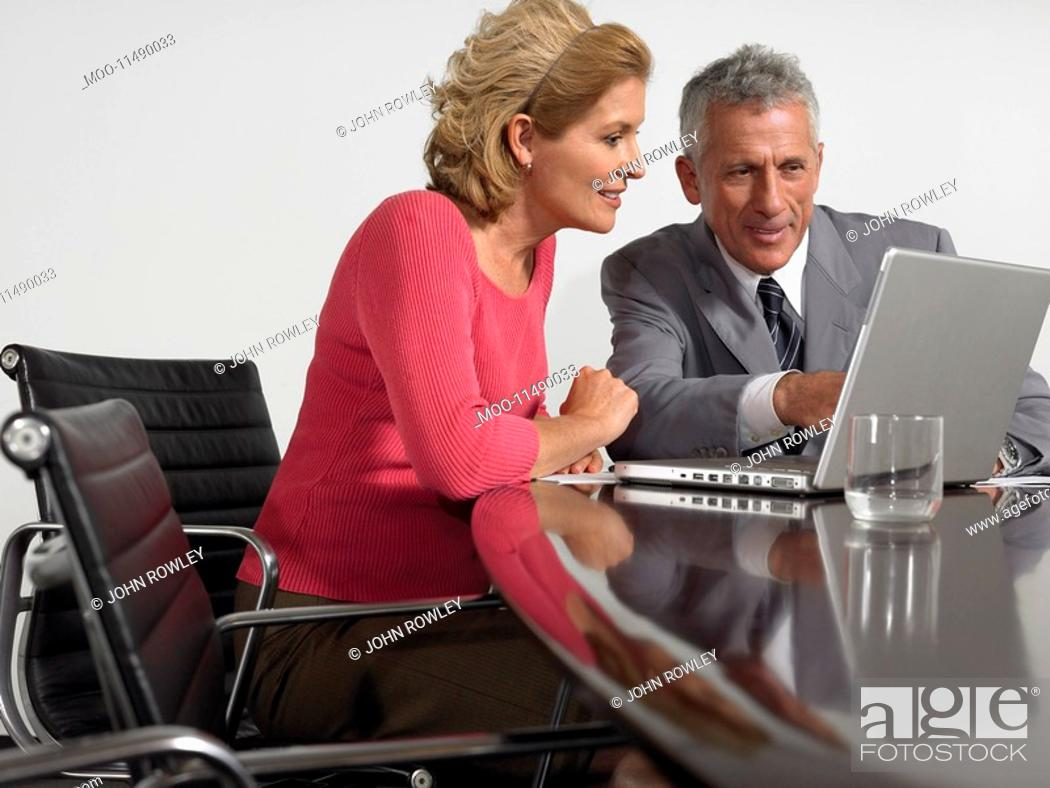 Stock Photo: Business colleagues using laptop at conference table.