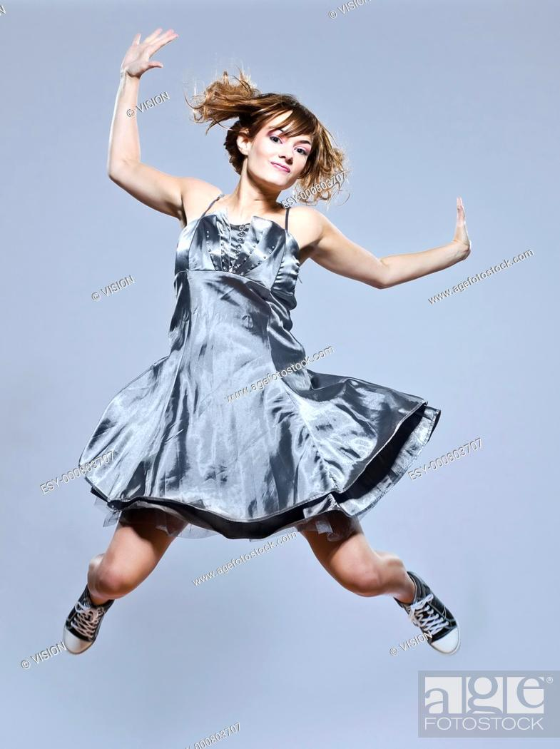 Stock Photo: beautiful young caucasian woman girl evening dress jumping happy on studio isolated plain background.