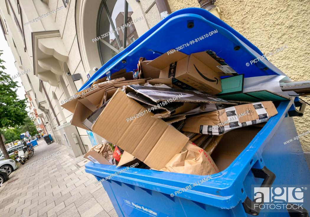 Photo de stock: 16 July 2020, Bavaria, Munich: An overflowing paper container is waiting in front of a house for collection by the waste collection service.