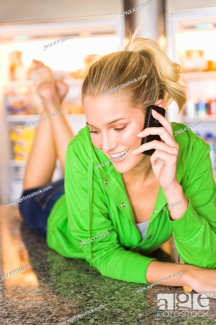 Stock Photo: Woman lying on the kitchen counter and talking on a mobile phone.