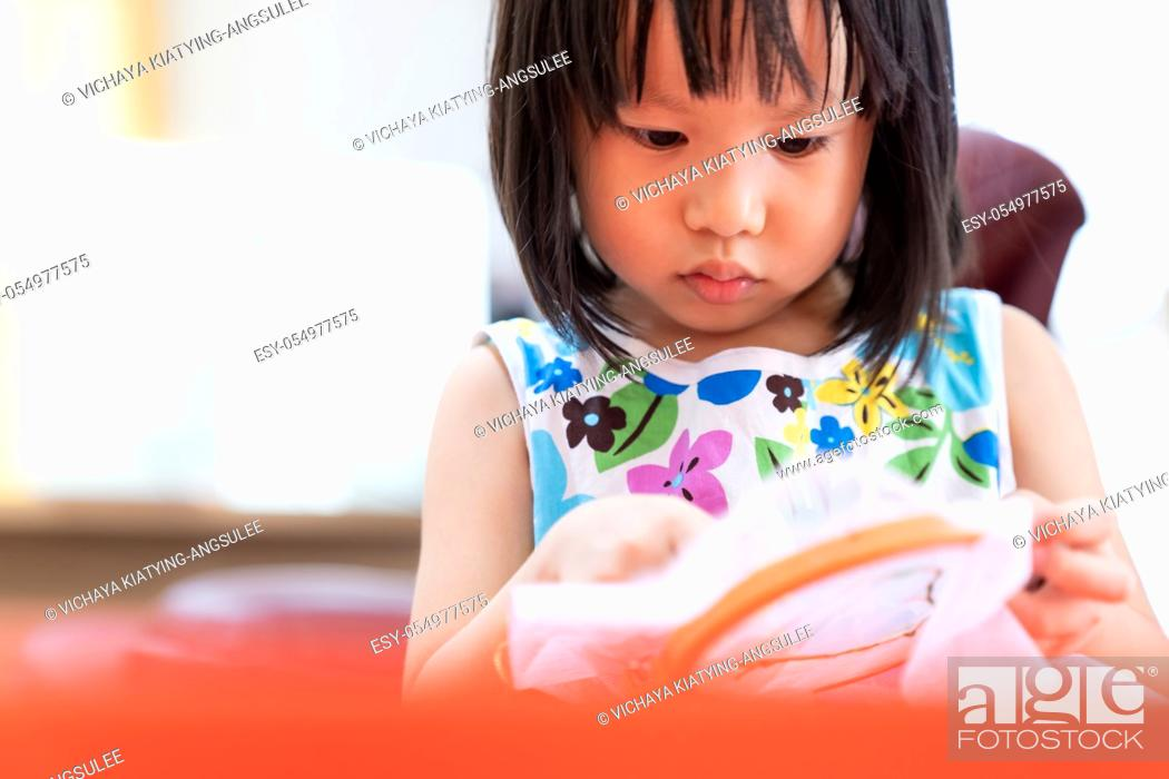 Stock Photo: Asian girl child sewing in living room at home as home schooling while city lockdown because of covid-19 pandemic across the world.