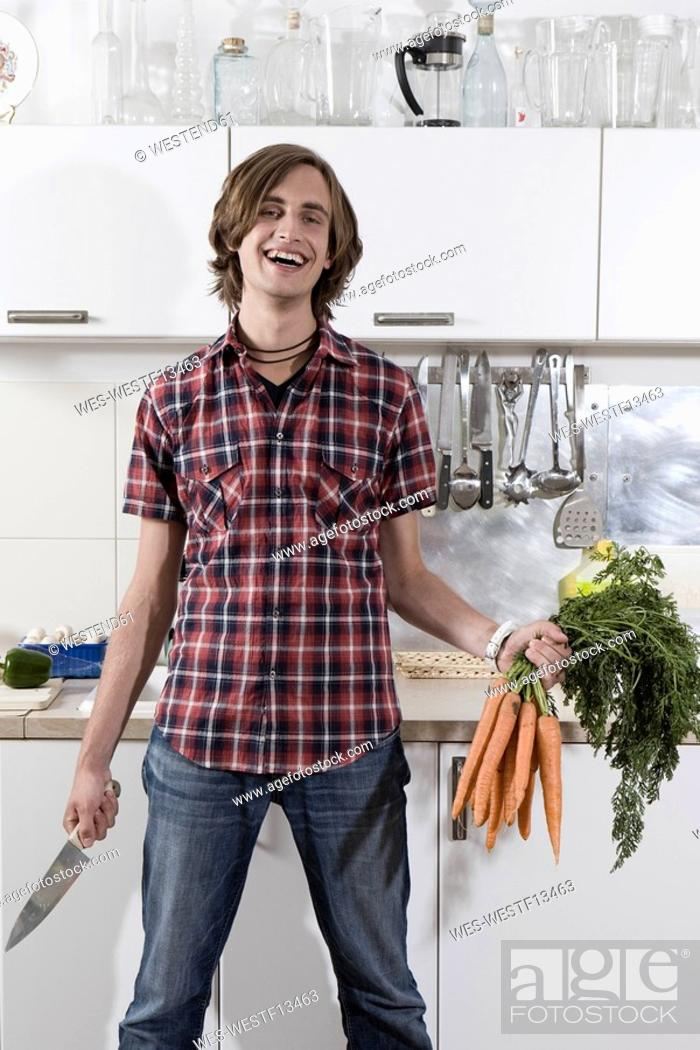 Stock Photo: Germany, Berlin, Young man in kitchen holding bunch of carrots and knife, laughing, portrait.