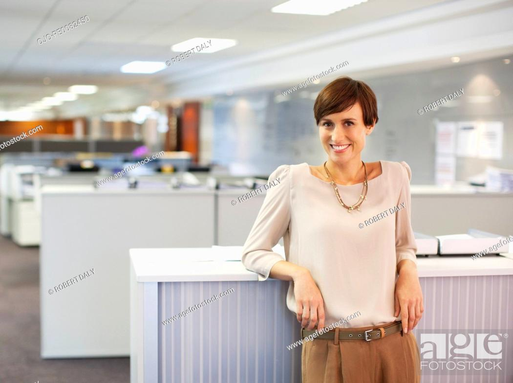 Stock Photo: Portrait of smiling businesswoman in office.