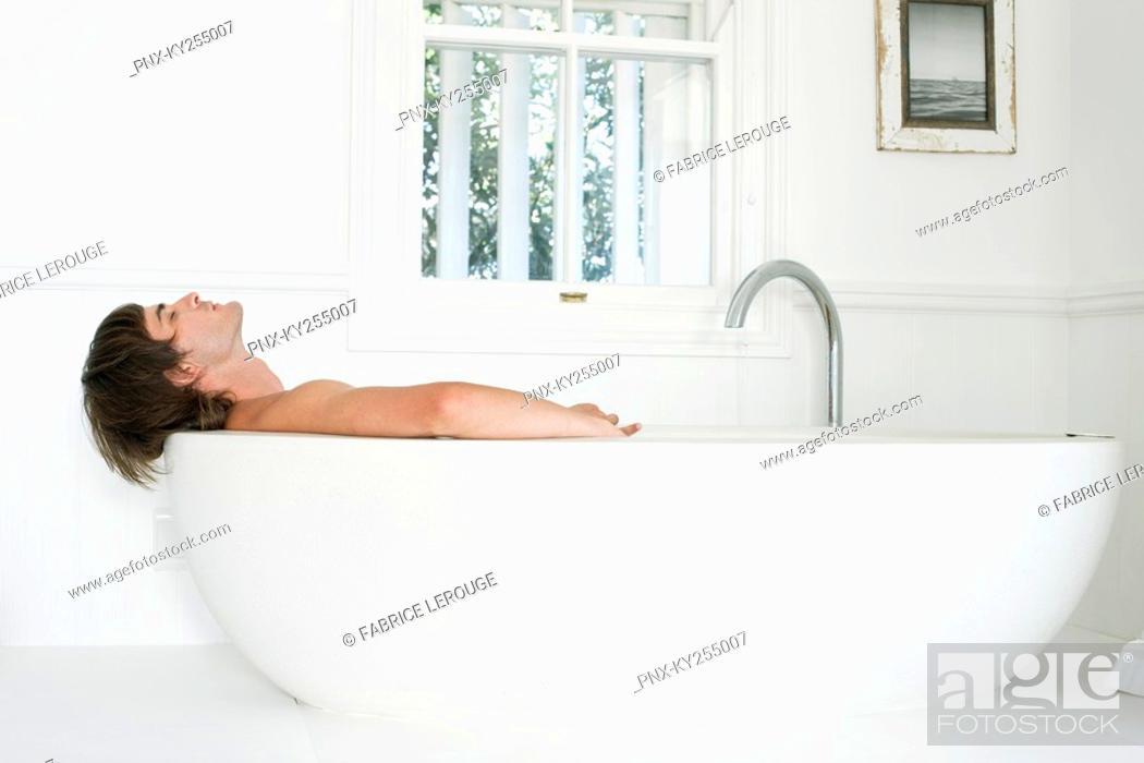 Stock Photo: Man lying in a bathtub.