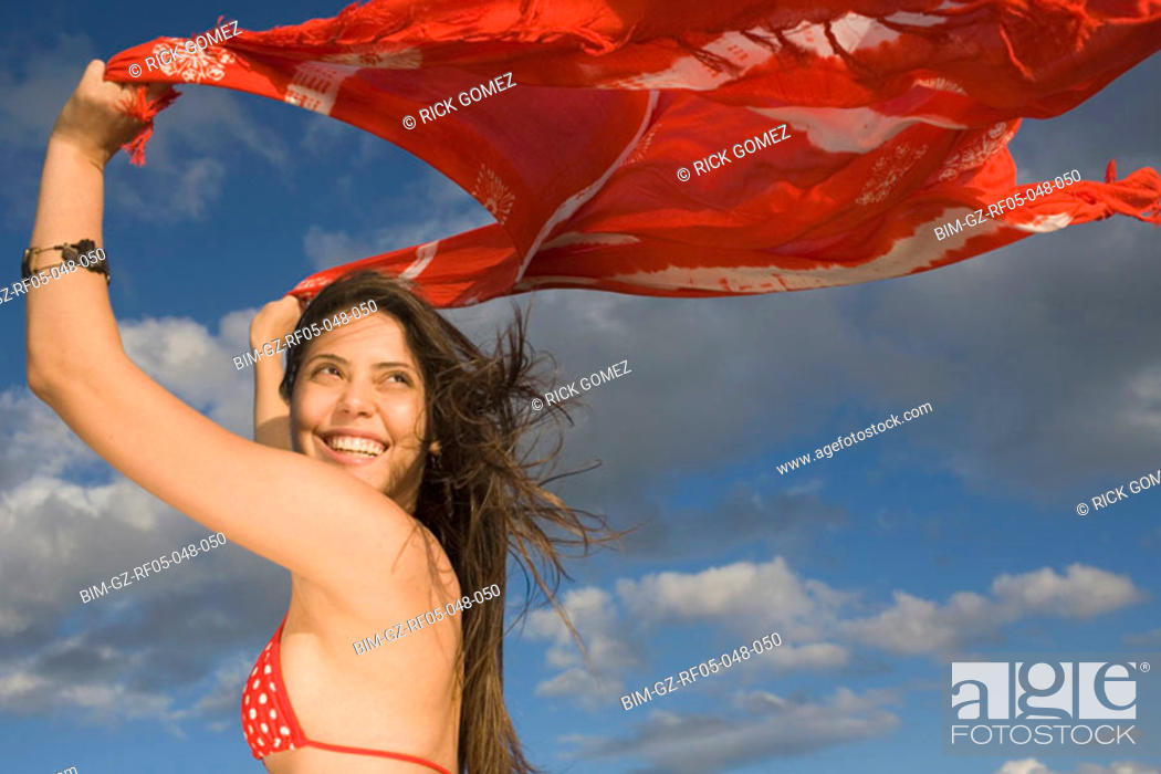 Stock Photo: Young woman holding shawl over her head in the wind.
