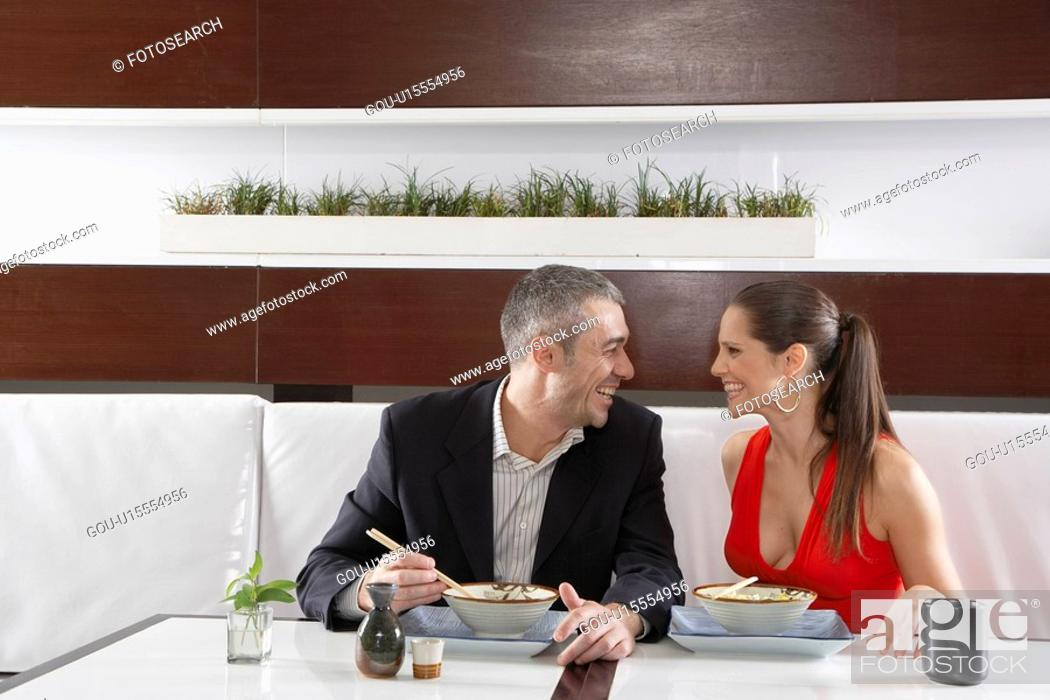 Stock Photo: Couple eating noodles in restaurant.