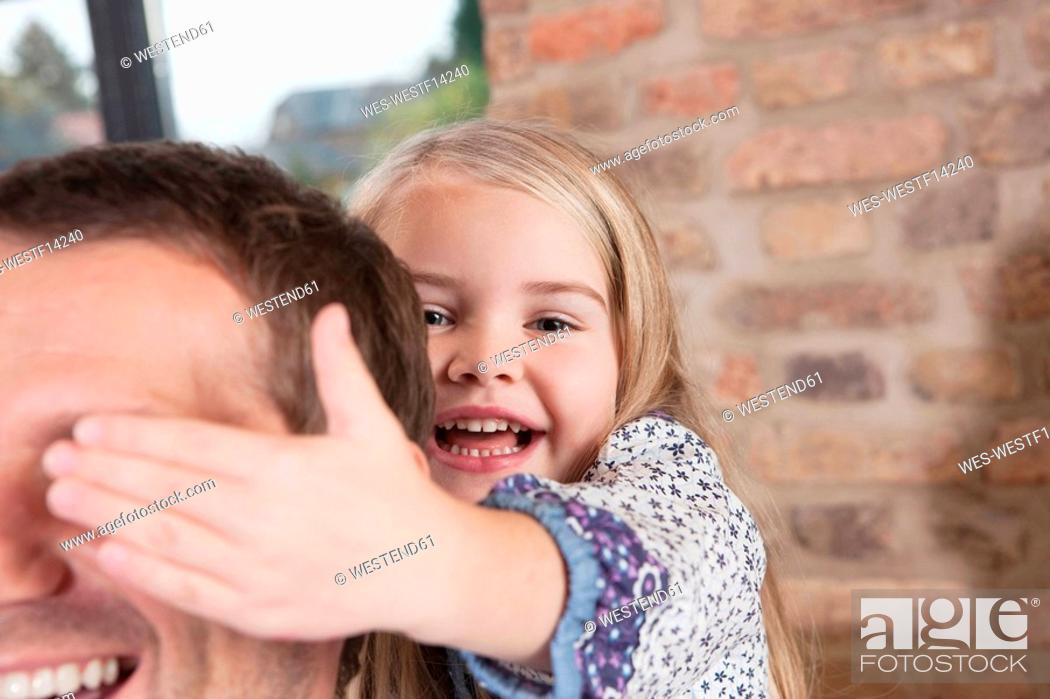 Stock Photo: Germany, Cologne, Girl 6-7 covering father's eyes, portrait, close-up.