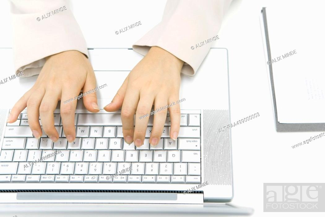 Stock Photo: Person typing on laptop computer, cropped view of hands, overhead view.