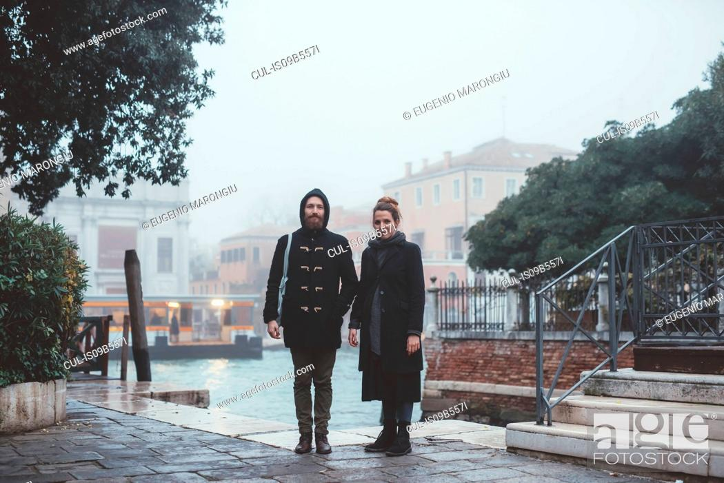 Imagen: Portrait of couple standing by misty canal, Venice, Italy.