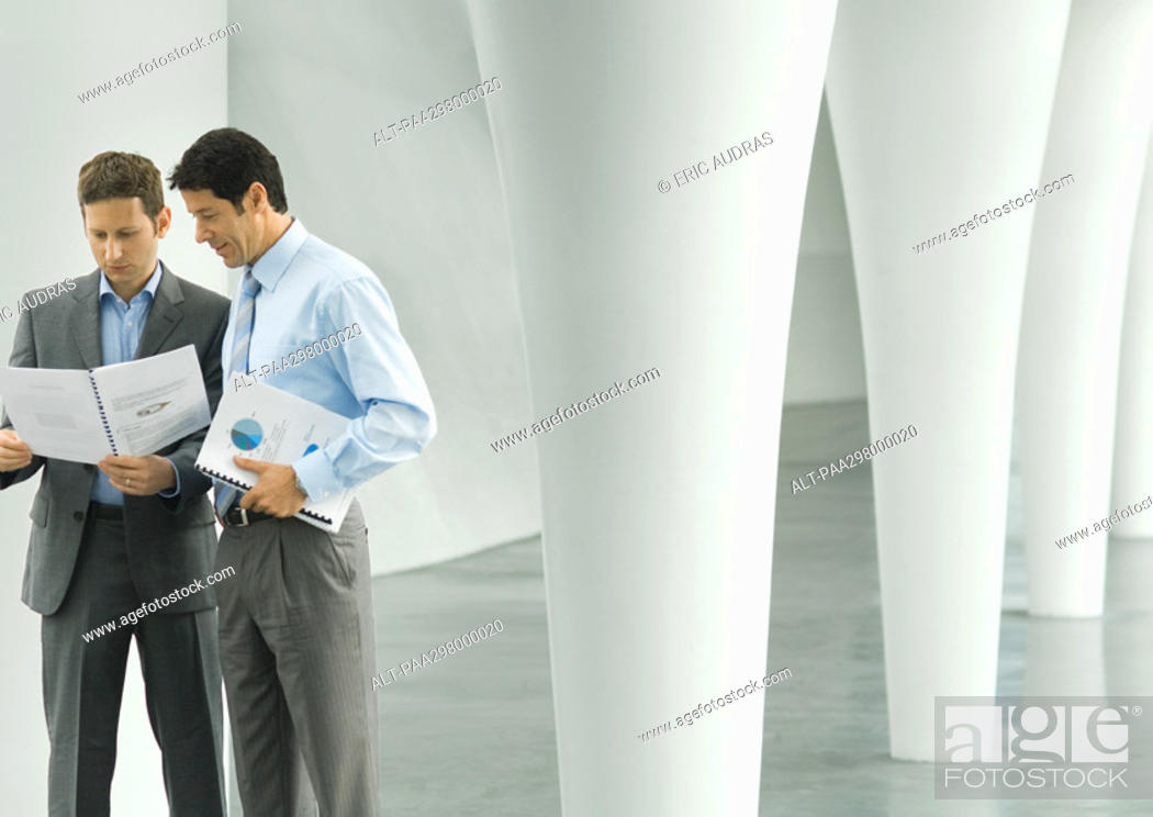 Stock Photo: Two businessmen looking at documents in lobby.