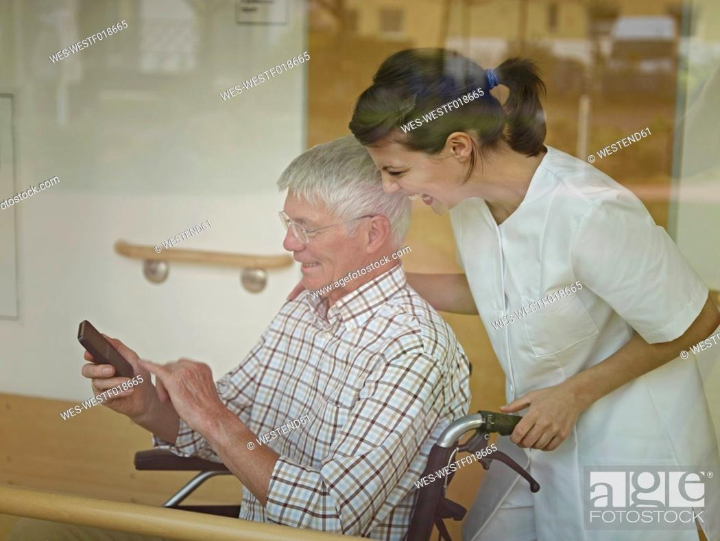 Stock Photo: Germany, Cologne, Senior man sitting in wheelchair and dialling cell phone, caretaker standing beside.