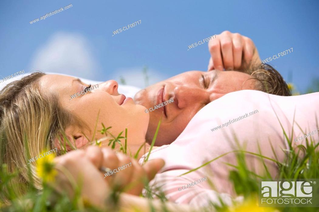 Stock Photo: Germany, Bavaria, Munich, Young couple lying in meadow.