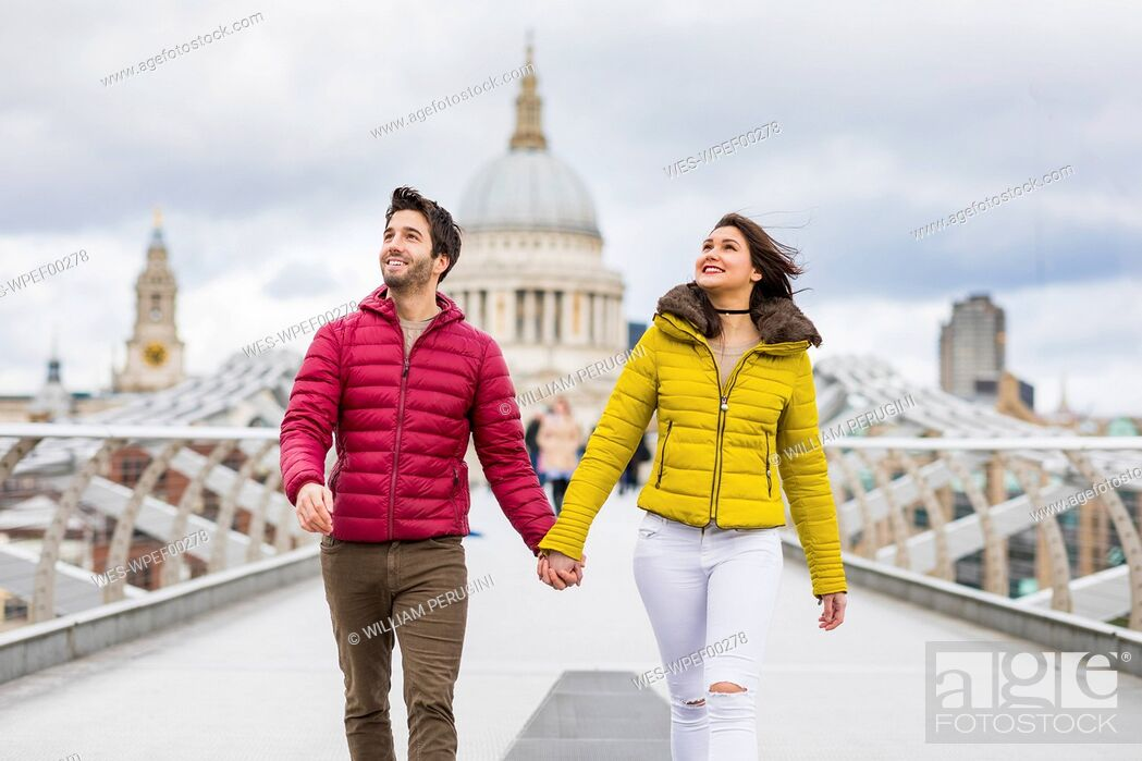 Imagen: UK, London, young couple walking hand in hand on bridge in front of St Pauls Cathedral.