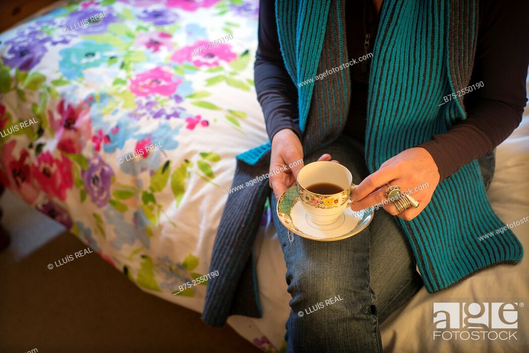 Stock Photo: Midle Age Lady, relaxed and calm, seating on the bed side with a cup of coffee in hand.