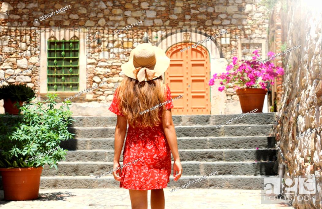 Stock Photo: Curious young woman with red dress and hat walking in street in Taormina, Italy. Rear view of happy cheerful girl visiting Sicily Island.