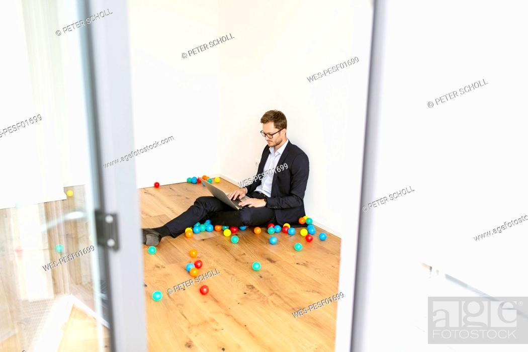 Stock Photo: Businessman sitting on the floor using laptop surrounded by colourful balls.