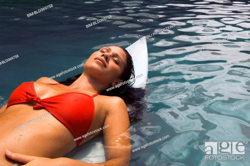 Stock Photo: Pacific Islander woman laying on surfboard in water.
