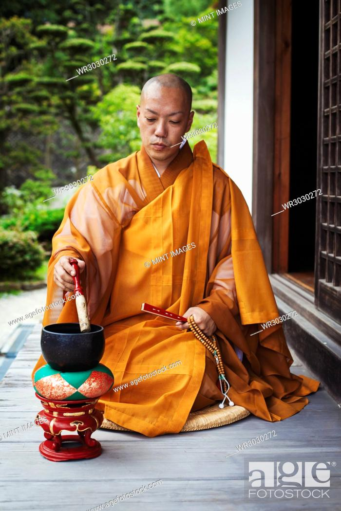Stock Photo: Buddhist monk with shaved head wearing golden robe sitting on floor outdoors, using singing bowl.