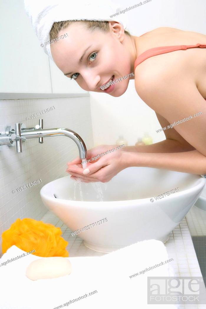 Stock Photo: Young woman washing face, side view, portrait.