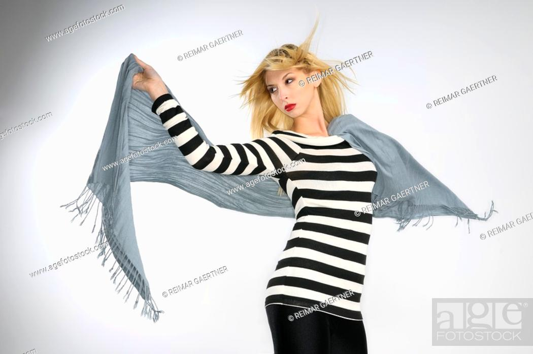 Stock Photo: Young blond woman in striped top holding a scarf in the wind on gray background.