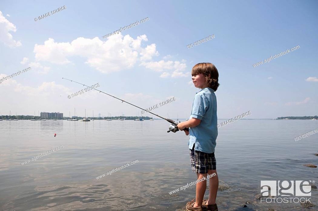 Stock Photo: Young boy fishing on beach.
