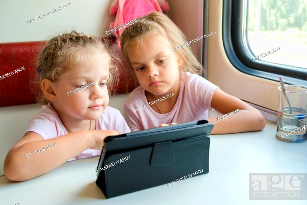 Stock Photo: Two girls sisters sitting in the train watching a cartoon in the plate.