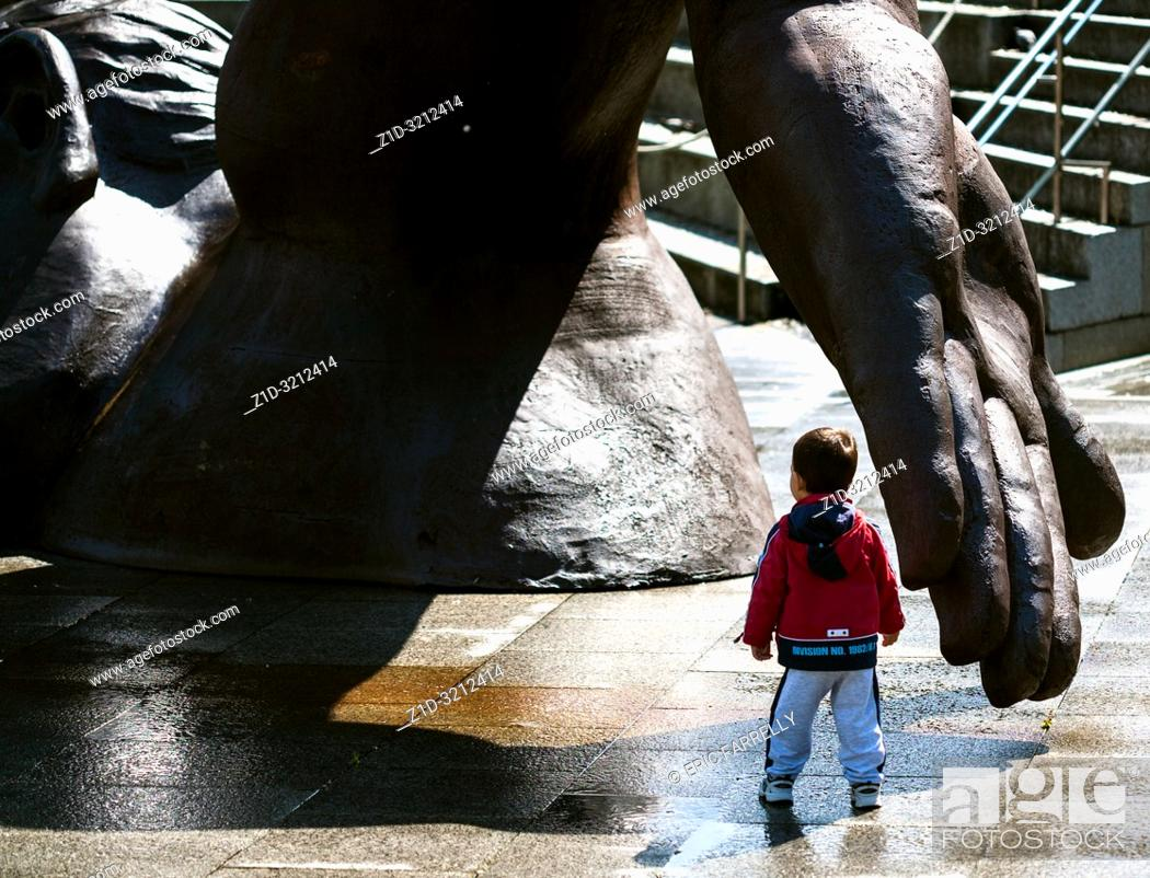 """Imagen: young boy curious about Sculpture """"Banista no areal 2"""" (the swimmer) by Francisco Leiro at Vigo Seafront Spain."""