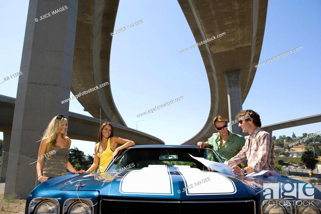 Stock Photo: Two young couples by car beneath overpass, low angle view.