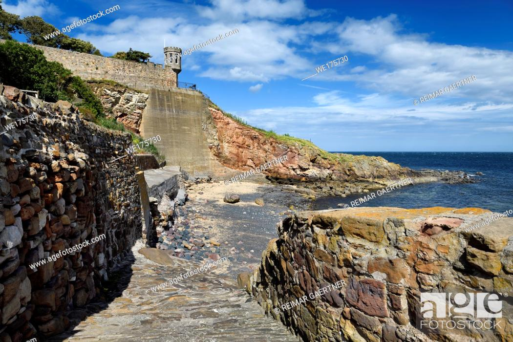 Stock Photo: Rock wall path to beach at Crail in Fife Scotland UK with lookout tower turret of Crail House over the North Sea.