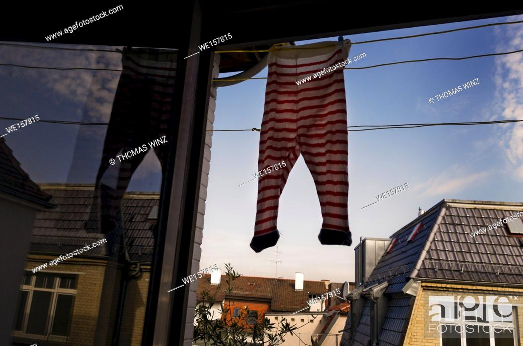 Stock Photo: Baby clothes hanging to dry at a balcony door. Stuttgart, Germany.