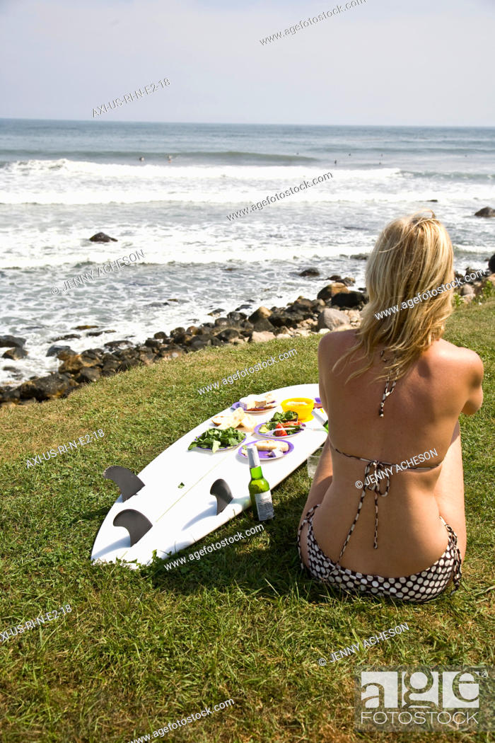 Stock Photo: Girl in bikini with surfboard laid out with a picnic.