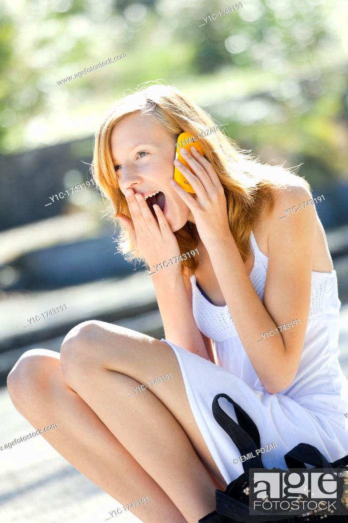 Stock Photo: Laughing young woman uses cellphone.