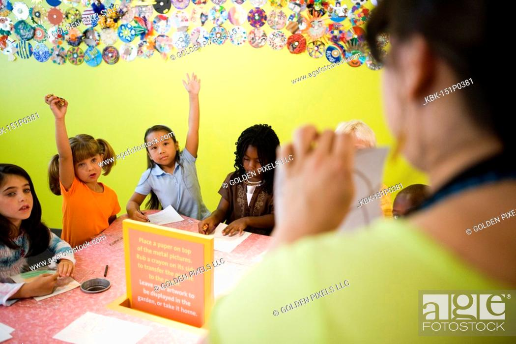 Imagen: An art teacher demonstrating an art project to her young students in art class.