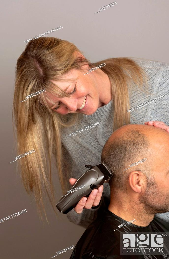 Stock Photo: Woman using portable electric hair clippers to give a balding man a crew cut.