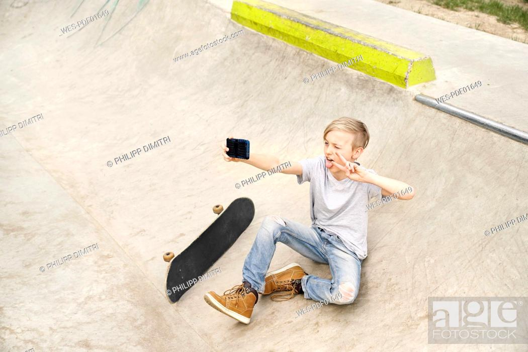 Stock Photo: Boy with skateboard taking selfies with smartphone.